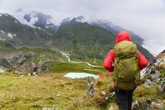 远足艰苦跋涉的远足者在与背包的山 免版税库存照片