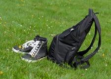 远足袋子和起动在草 免版税库存图片