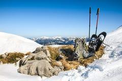 远足设备的冬天 背包和雪靴在山顶部 免版税图库摄影