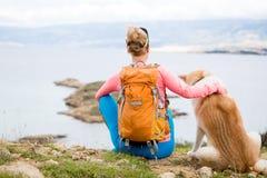 远足走与在海风景的狗的妇女 免版税库存图片
