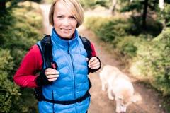 远足走与狗的愉快的妇女 免版税库存图片