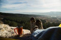 远足起动和一个杯子在自然背景  免版税库存照片