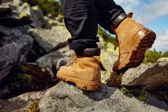 远足起动特写镜头 在山行迹的女孩旅游步在岩石 免版税库存图片