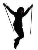 远足跳跃的愉快的剪影的妇女远足者 免版税图库摄影