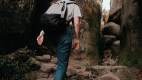 远足迁徙在山 一名年轻曲棍球妇女的后面的背面图走与背包的 股票录像