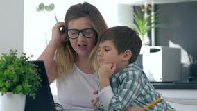 远距离学习,孩子做与他的母亲的家庭作业在与膝上型计算机的桌上坐厨房 影视素材