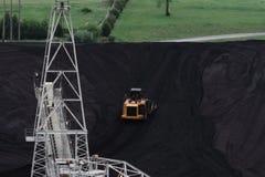 远离传送带的推土机移动的煤炭 库存图片