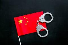 违反法律,违法的概念 在中国旗子的金属手铐在黑背景顶视图 库存照片