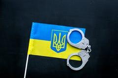 违反法律,违法的概念 在乌克兰旗子的金属手铐在黑背景顶视图 免版税库存图片