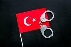 违反法律,违法的概念 在土耳其旗子的金属手铐在黑背景顶视图 图库摄影
