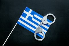 违反法律,违法的概念 在希腊旗子的金属手铐在黑背景顶视图 免版税库存照片