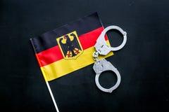 违反法律,违法的概念 在德国旗子的金属手铐在黑背景顶视图 库存照片
