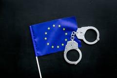 违反法律,违法的概念 在欧洲旗子的金属手铐在黑背景顶视图 库存图片
