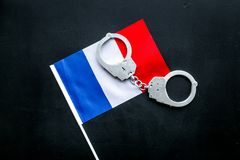 违反法律,违法的概念 在法国旗子的金属手铐在黑背景顶视图 免版税库存图片