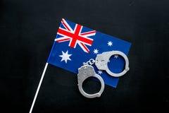 违反法律,违法的概念 在澳大利亚旗子的金属手铐在黑背景顶视图 图库摄影