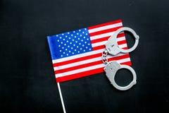 违反法律,违法的概念 在美国的金属手铐,在黑背景顶视图的美国旗子 免版税库存图片