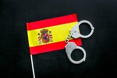 违反法律,违法的概念 在西班牙旗子的金属手铐在黑背景顶视图 免版税库存照片