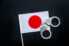 违反法律,违法的概念 在Japaniese旗子的金属手铐在黑背景顶视图 库存照片