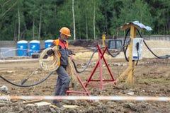 连接一个电缆的建造场所的电工 免版税库存照片