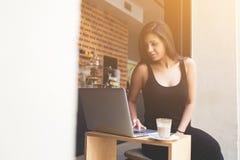 连接到无线的华美的拉丁妇女通过网书,当在咖啡店时的早餐 免版税库存图片