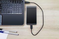 连接到膝上型计算机的智能手机由在木书桌上的usb缆绳用笔和纸 免版税图库摄影