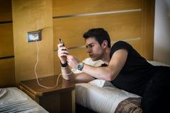 连接电话的严肃的年轻人到充电器 免版税库存图片