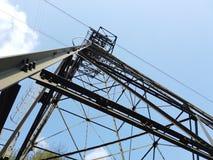连接白变种和塞尔维诺镇空中览绳的定向塔 伪装他们的绿色被绘的定向塔在森林 图库摄影