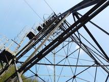 连接白变种和塞尔维诺镇空中览绳的定向塔 伪装他们的绿色被绘的定向塔在森林 库存图片