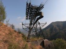连接白变种和塞尔维诺镇空中览绳的定向塔 伪装他们的绿色被绘的定向塔在森林 免版税库存图片