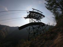 连接白变种和塞尔维诺镇空中览绳的定向塔 伪装他们的绿色被绘的定向塔在森林 免版税库存照片
