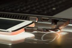 连接的智能手机和膝上型计算机有USB缆绳的 免版税库存照片