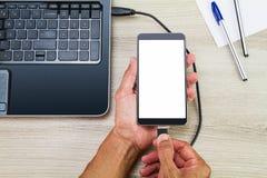 连接空白的白色屏幕智能手机的手到膝上型计算机通过使用usb在有笔和纸的木书桌上缚住 免版税库存图片