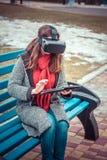 连接虚拟现实VR和片剂的女孩 免版税库存图片