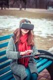 连接虚拟现实VR和片剂的女孩 图库摄影