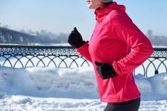 连续体育运动妇女 跑步在寒冷冬天城市的母赛跑者戴着温暖的运动的连续衣物和手套 免版税图库摄影