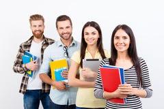 连续站立和微笑在casualw的小组愉快的学生 免版税库存图片