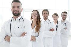 连续站立在医院的小组愉快的成功的医生 库存图片