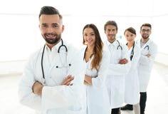 连续站立在医院的小组愉快的成功的医生 免版税库存图片