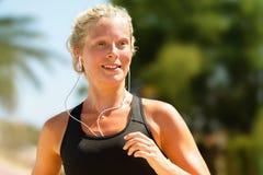 连续与耳机的女孩冒汗的锻炼 免版税图库摄影