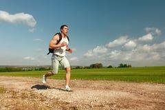 连续在足迹的人冲刺的十字架 马拉松的男性适合的体育健身模型训练外面在美好的风景 免版税图库摄影