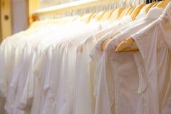 连续垂悬在机架的白色外套 免版税库存图片