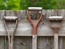 连续垂悬在老木fe的年迈的木园艺工具 免版税库存照片