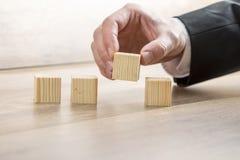 连续安置四个木立方体的男性手 库存图片