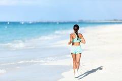 连续成套装备的运动的赛跑者训练心脏跑步在晴朗的海滩的 免版税库存图片