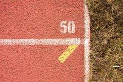 连续跑马场,红色橡胶跑马场空白线路和纹理在小体育场内 库存图片