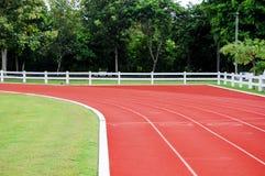 连续轨道和体育领域在绿色自然围拢 库存照片