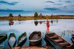 迟来的 钓鱼从老木划艇的白俄罗斯语孩子在夏天期间 免版税库存图片