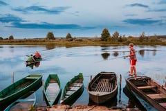 迟来的 钓鱼从老木划艇的白俄罗斯语孩子 库存照片