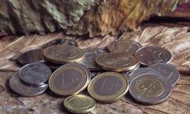 迪拉姆阿拉伯硬币和在葡萄酒背景的欧洲硬币 免版税库存照片