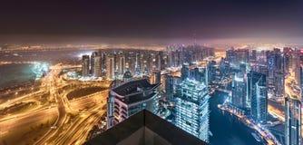 迪拜天际在朦胧的夜点燃发光有一个美好的全景塔屋顶视图 库存照片
